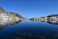 Parkerar gräsplan för blå himmel för bergnaturen wood den trevliga molnsjöreflexet Royaltyfri Foto