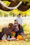 Parkerar gravida par för härligt barn som har picknicken i höst Mummel Arkivfoton