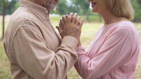 Parkerar hållande kvinnans för den åldriga mannen hand, det romantiska datumet in, pålitlighet, affektion arkivfilmer