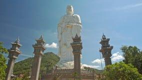 Parkerar höga kolonner för nära stor vit Buddhastaty i tempel arkivfilmer