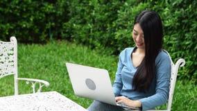 Parkerar kopplar av den härliga asiatiska unga kvinnan för ståenden som sitter i, genom att använda bärbar datordatoren hemma för stock video