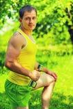 Parkerar lyftande vikter för stilig ung idrottsman i gräsplan instagram arkivbilder