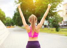Parkerar lyfter den lyckliga löparekvinnan för kondition som tycker om, efter utbilda i stad, löparevinnaren, händer upp, sporten Royaltyfri Bild