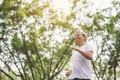 Parkerar mogen manspring för den asiatiska pensionären som in joggar royaltyfria bilder