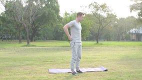 Parkerar rullande yoga för den unga stiliga mannen som är matt, når den har mediterat på arkivfilmer