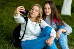 Parkerar sammanträde för den tonårs- flickan för två skolflickor på gräs i sommar in I hans handhåll tar en smartphone, bilder av fotografering för bildbyråer