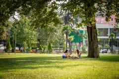 Parkerar sammanträde för ung kvinna som två vilar under ett stort träd i en stad royaltyfri fotografi