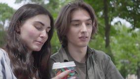 Parkerar unga lyckliga par f?r st?ende i tillf?llig kl?der som spenderar tid tillsammans i och att ha ett datum Dricka för studen stock video