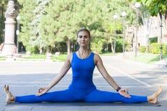 Parkerar utomhus- praktiserande yoga för den unga kvinnan in royaltyfri bild