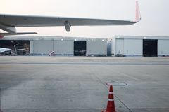 Parkerat flygplan nära hangaren Lastnivå på flygfältet Kommersiella flygfrakter Solnedgång som spotting på flygplatsen - Bild arkivfoto