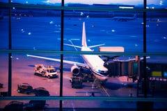 Parkerat flygplan på den beijing flygplatsen till och med portfönstret royaltyfria foton
