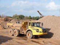 Parkerat gult villebråd som tippar stora hjul för lastbilkonstruktion royaltyfri bild