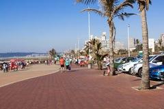 Parkerat medel och folk på strandframdel arkivfoton