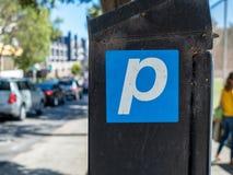 Parkerensymbool op een parkerenmachine wordt gekleefd voor straatparkeren in stad die stock afbeelding