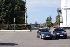 Parkeringen av bilar nära den Syzran Kreml mot bakgrunden av monumentet till soldaterna, som dog i lokal, krigar staden Arkivfoton