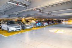 Parkeringsgarage med parkerade bilar Arkivbilder