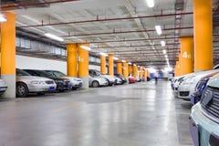 Parkeringsgarage, underjordisk inre med några parkerade bilar Arkivbild