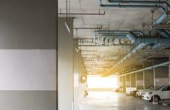 Parkeringshus i andelslägenhetfokusen på betongväggen och suddighetsbakgrund Arkivbild