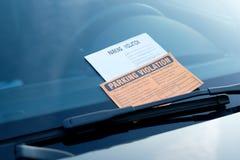 Parkeringskränkningbiljett fint på vindrutan Royaltyfri Foto