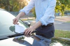 Parkeringskränkningbiljett fint på vindrutan Royaltyfri Fotografi