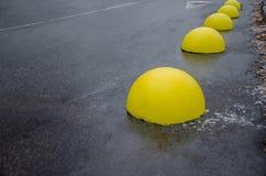 Parkeringslimiter Konkreta bollar på asfalt arkivbild