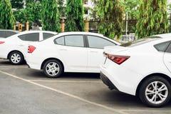 Parkeringsplatsen på det öppet och där är en parkerad bil Det finns träd omkring royaltyfri bild