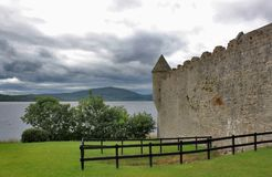 Old Irish castle on lake with mountain background royalty free stock photo