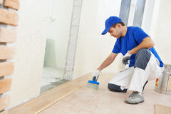 Parkettarbetare som tillfogar lim på golv arkivbild
