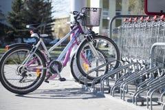 Parkfahrräder in einem parcking Gestell vor Supermarkt Lizenzfreie Stockfotografie