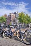Parkfahrräder gegen Geländer auf Brücke, Amsterdam, die Niederlande lizenzfreie stockbilder