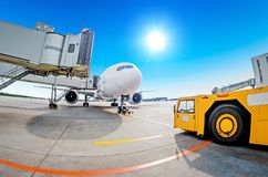 Parking at the airport, airplane at the teletrap. Aerodrome tractor is ready for towing and departure of the aircraft. Against the Royalty Free Stock Photos