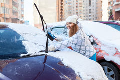 Parking area - young woman removing snow from own car Stock Images