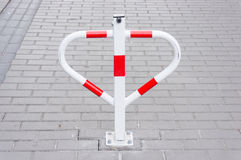Parking blocker. Metal parking blocker on stone pavement royalty free stock photography