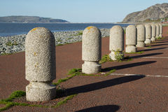 Parking bollards. A set of concrete precast parking bollards stretch into the distance with a path, pebble beach and the sea in the distance Stock Photo