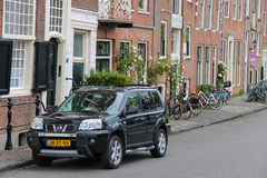 Parking car and bicycles near old buildings in city centre. Haarlem, the Netherlands - June 20, 2015: Parking car and bicycles near old buildings in the historic Royalty Free Stock Photos