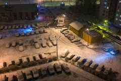 Parking cars under colored lights in the snow on New Year's Royalty Free Stock Photography