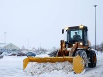 Parking de dégagement de machine de déblaiement de neige pendant la tempête de neige photo libre de droits