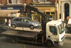 Parking Enforcement: Car Being Removed. A car is being lifted onto a truck after a parking infringment royalty free stock photo