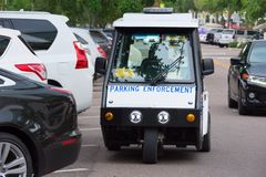 Parking Enforcement vehicle by parked cars to check parking mete Royalty Free Stock Image