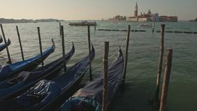 Parking gandolas on the Doge's palace embankment with the bell tower of the Saint Giorgio Maggiore church view. stock footage