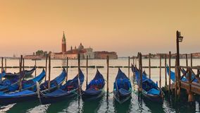 Parking gandolas on the Doge's palace embankment with the bell tower of the Saint Giorgio Maggiore church view. stock video footage