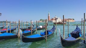 Parking gandolas on the Doge's palace embankment with the bell tower of the Saint Giorgio Maggiore church view. stock video