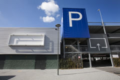 Parking garage with blank billboard. Blank billboard on a parking garage in Gouda. It's a public building with the entrance at the right side. A huge blue Stock Photos