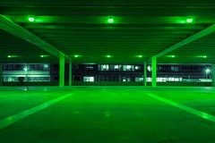 Parking garage with green light in free spots. Empty parking garage at night stock image