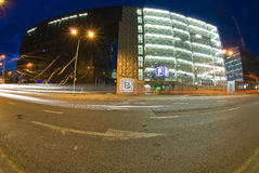 Parking garage at night. A wide angle, nighttime view of a multi-level parking garage with traffic streaks in the foreground Royalty Free Stock Image
