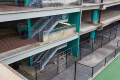 Parking garage with open staircase down to a fences in area. Horizontal aspect Stock Images