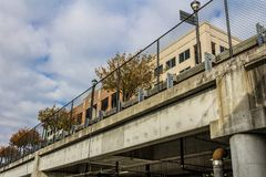 Parking garage under street with view to fencing, barriers, and buildings above Royalty Free Stock Image