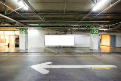 Parking garage underground interior with blank billboard.Empty space car park interior at night. Royalty Free Stock Images