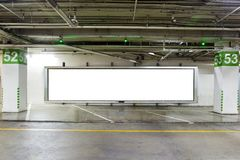 Parking garage underground interior with blank billboard.Empty space car park interior at night. Royalty Free Stock Photo