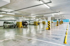 Parking garage, underground interior with a few parked cars. Stock Images